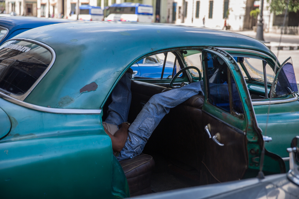 A taxi driver has a snooze in the back of his American car. Havana, Cuba, August 2015.