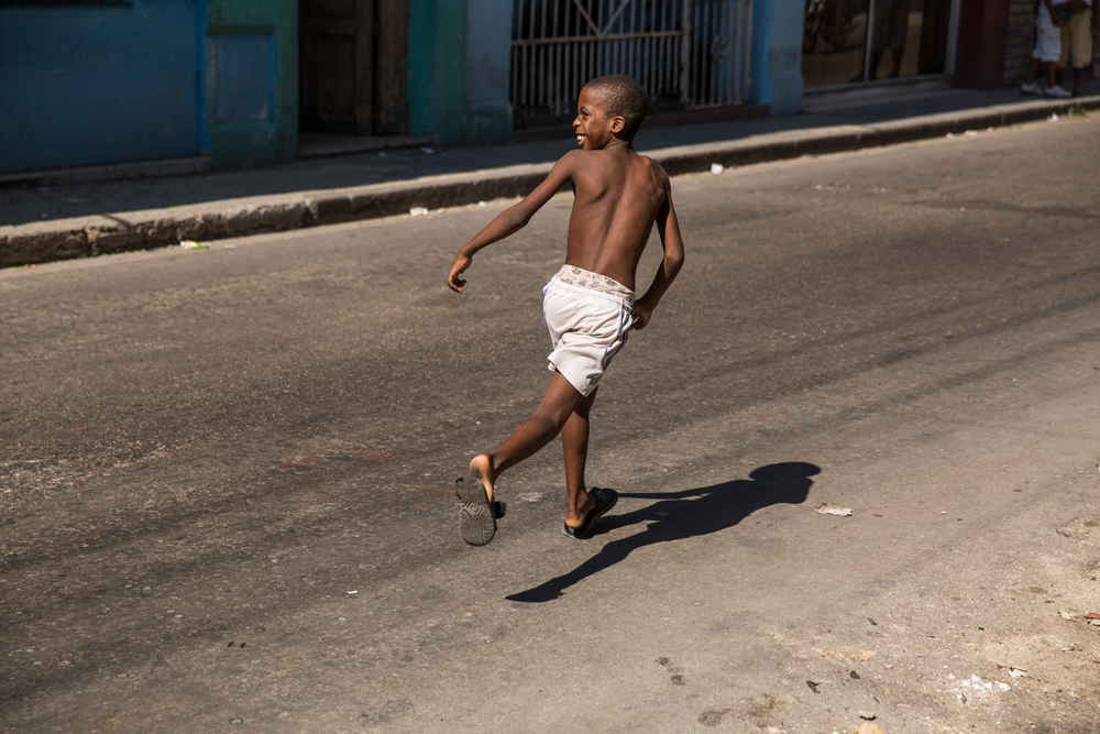 Cuban child playing in Havana street. Havana, Cuba, August 2015.
