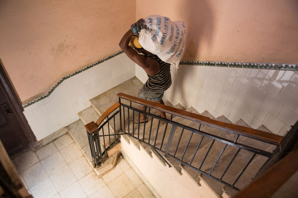 Man carrying rice from Vietnam down flights of stairs. Havana, Cuba, August 2015.