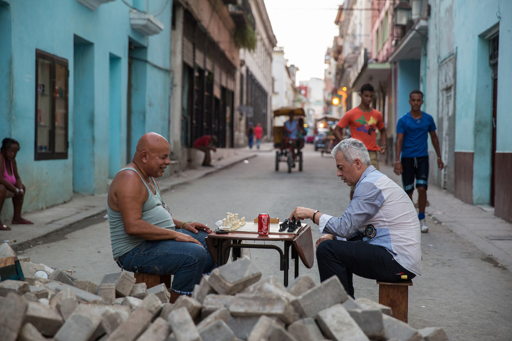 Two men play chess among a pile of bricks, dug up for some drain maintenance in Calle Obispo, Havana, Cuba, August 2015.