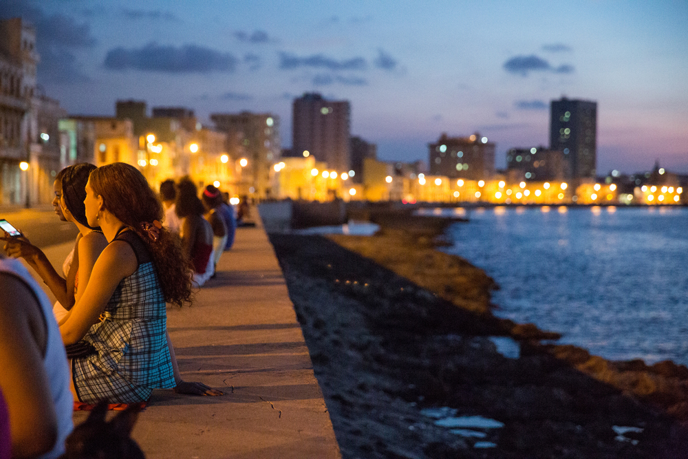 Local Cubans enjoy the respite from the heat along the Malecón in Havana, Cuba, August 2015.