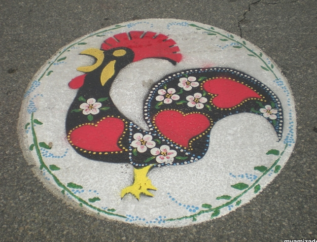 PORTUGUESE PRIDE The colorful Galo de Barcelos, Rooster of Barcelos, is a well-loved and easily recognized symbol of Portugal. It symbolizes honesty, integrity, trust and honor. This rooster, painted on the street in Portuguese Square, lets us know we're in the right place at the right time.