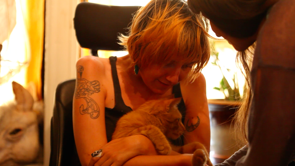 Aaron handing Lindsay her cat, Chicken during one of their sessions together in the Bronx