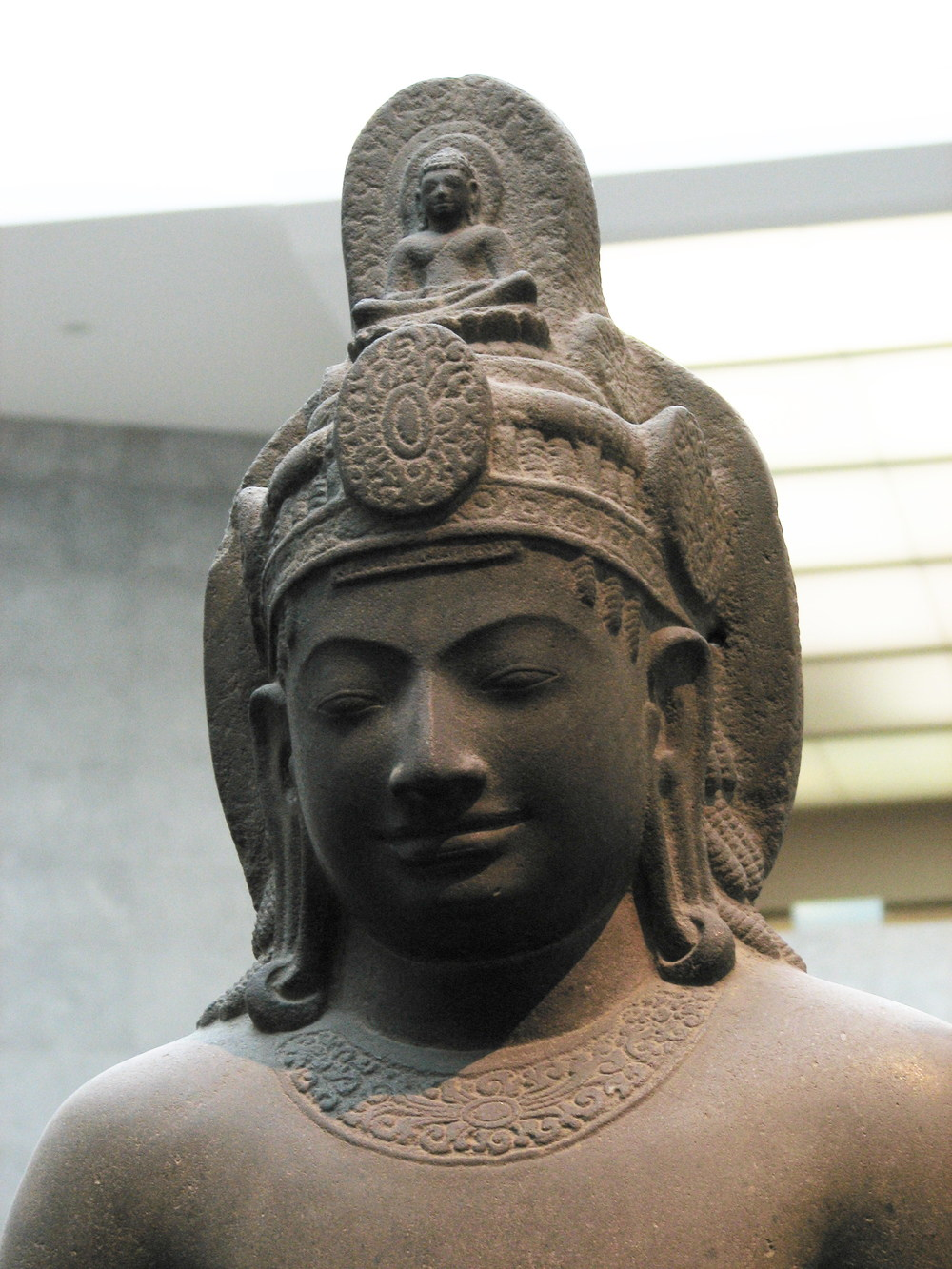 Cambodian statue of Avalokiteśvara Bodhisattva. Sandstone, 7th century CE. Many statues of this version of the Buddha feature the teacher seated on the crown.