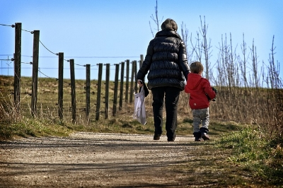 A mother and child walking away from the camera.