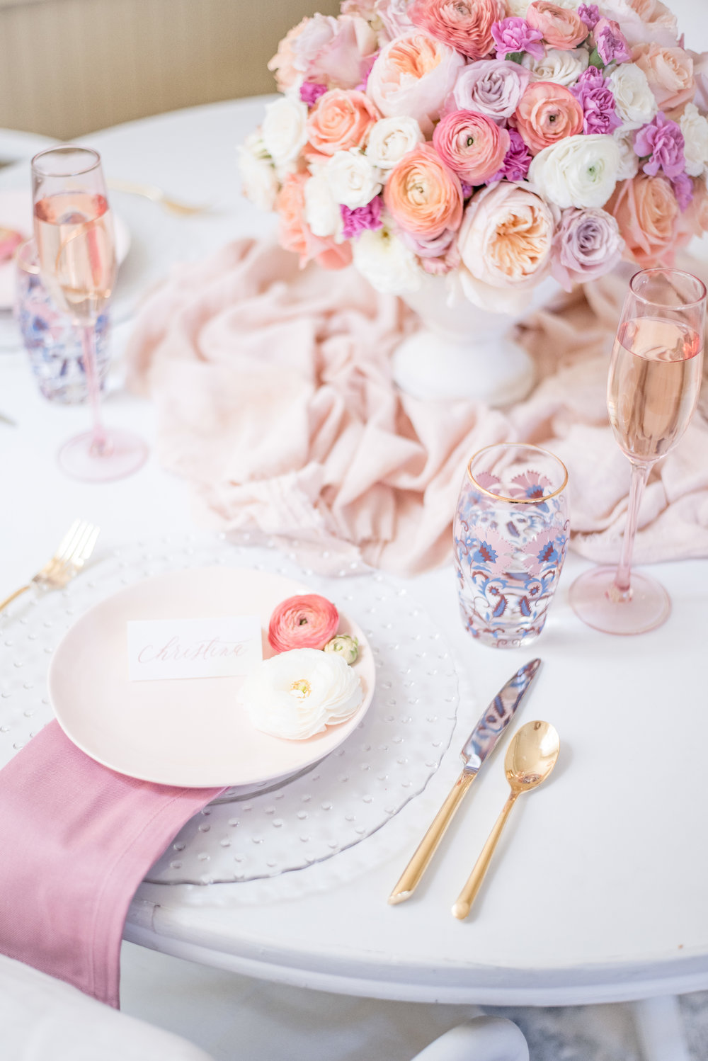 Gold flatware and festive patterned water glasses pair so well with pale pink plates and napkins!