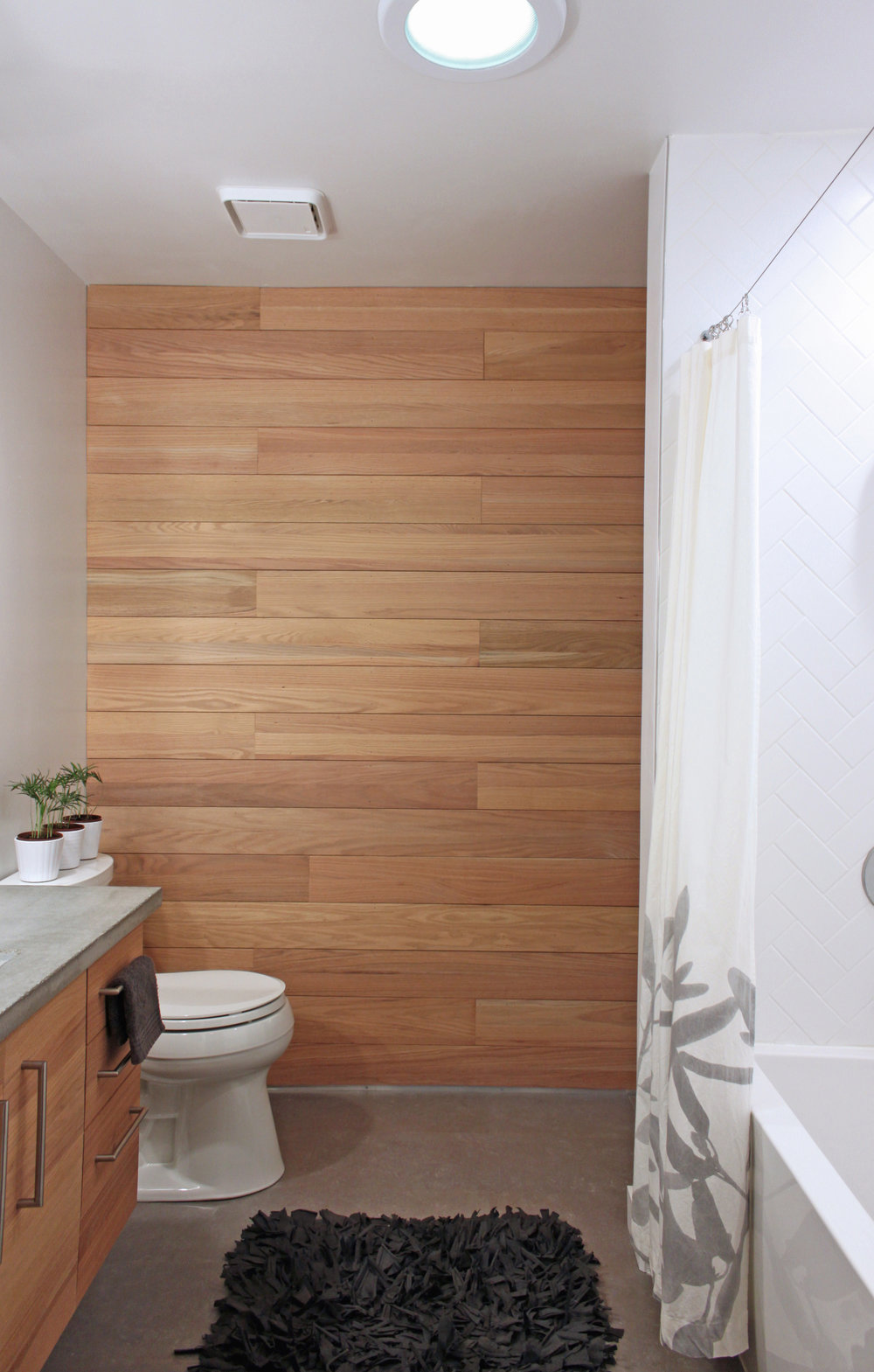 A 1970s bathroom remodel with a ton of green features. It includes cork flooring, concrete counter, natural lighting, herringbone subway tiles, and a red oak wall and vanity with water efficient fixtures.