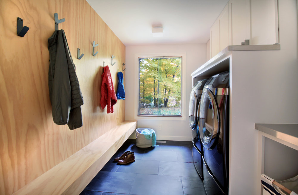 A multi-purpose mudroom and laundry. Forgoes the coat closet and features a plywood coat wall with floating bench. Heated slate tile floor and large window warm the space.