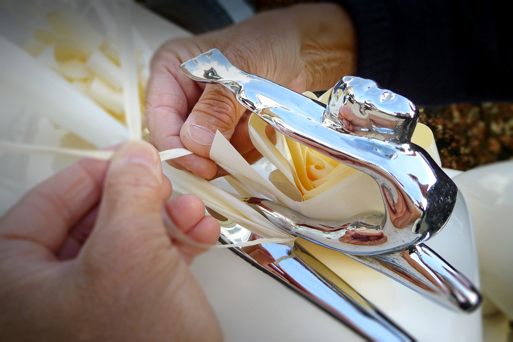 "Tying ivory ribbons to the mascot of our Beauford Tourer Wedding Car. Technology has now provided the ""pull bow"" which ensures perfection every time."