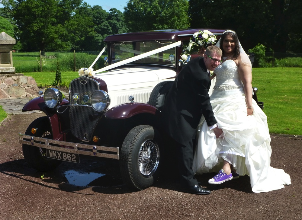 "Louise & Martin enjoying their ""fun"" wedding. We get to see many different versions of footwear as the Bride exits the car. Louise was proud to display her comfortable trainers - matching the bridesmaids dresses. The puddle under the car is not a leak. The remains of the mornings downpour!"