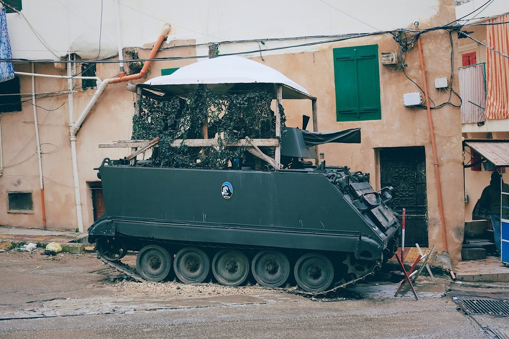 Camouflaged tank wearing small roof for added soldier comfort, hides near Tripoli's old castle.