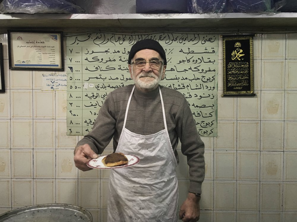 Tripoli man serving pastry with meat.