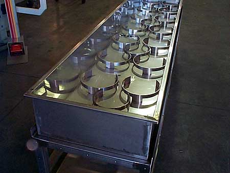 Stainless steel frame and sink designed for a water bath of manufactured products.