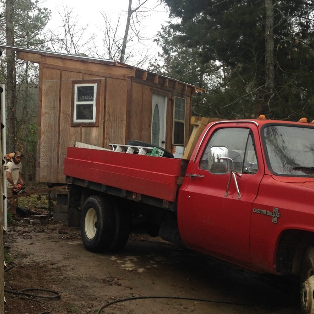 Travis carefully lowers the intern cabin onto the trailer for towing to the new farm.