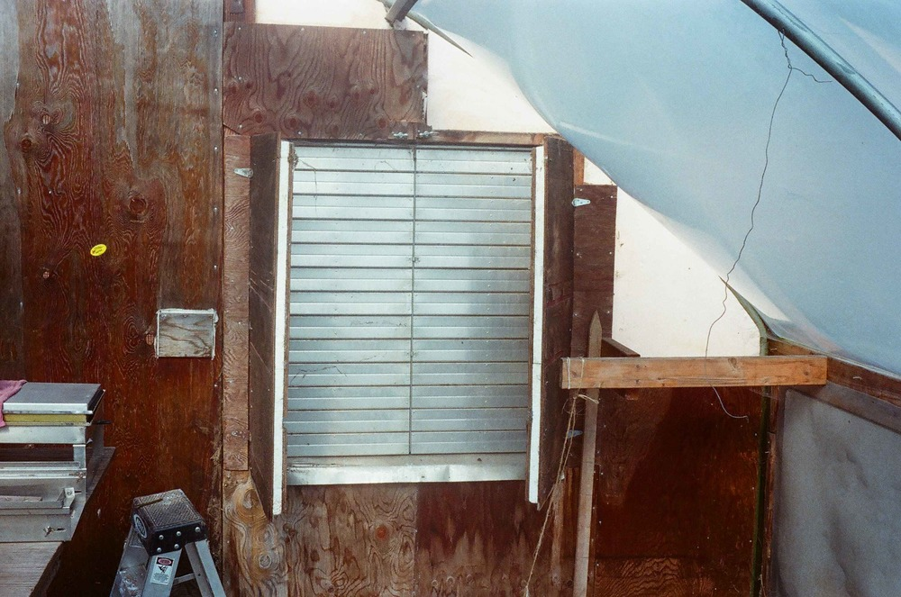 This air shutter allows fresh air into the greenhouse on warm days. The insulated doors are closed at night to prevent heat loss. The wooden end walls, surrounding the shutters, are also insulated.