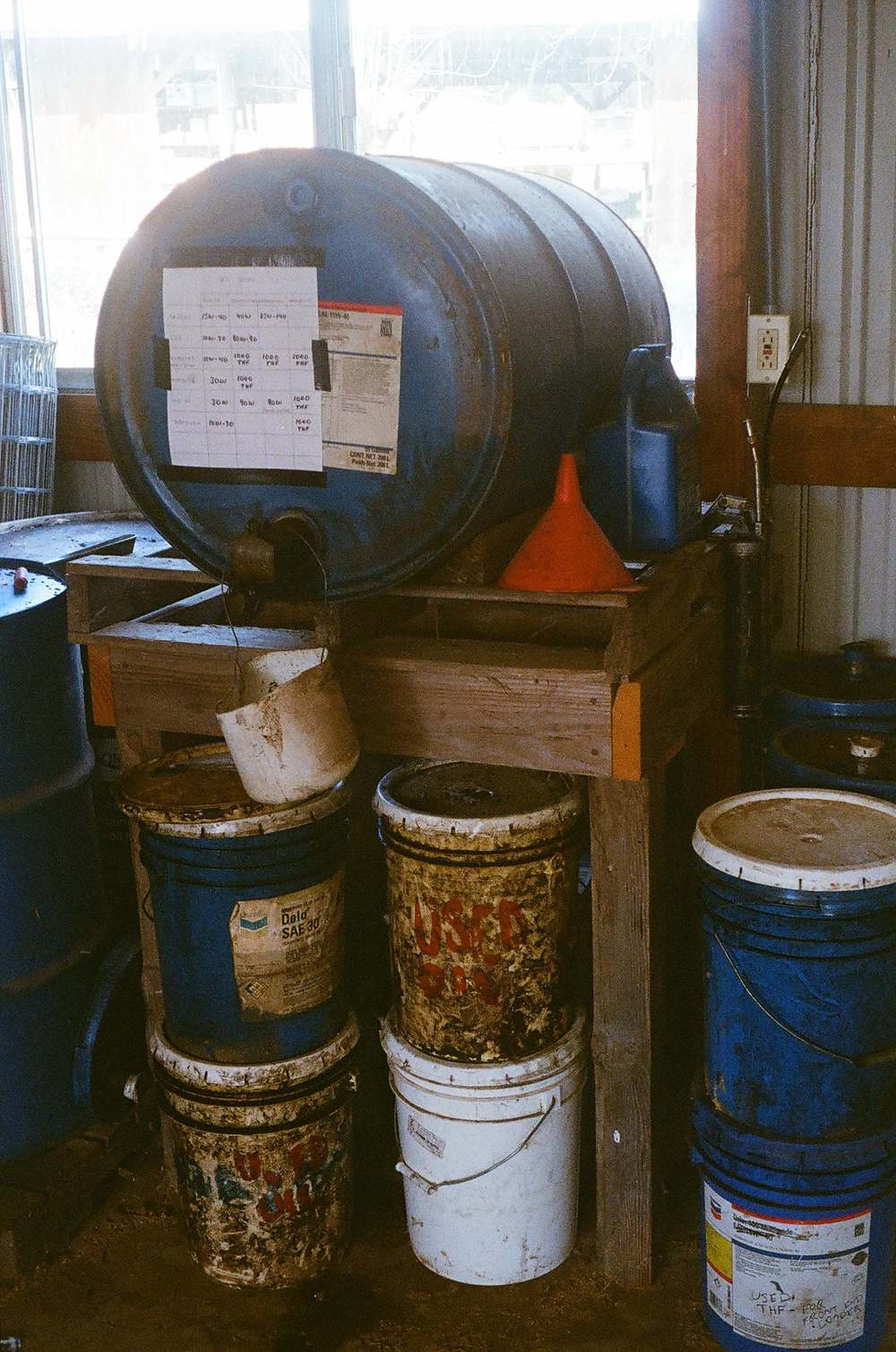 Motor oil is purchased in reusable drums rather than nonrecyclable plastic containers. These buckets on the floor hold used oil that is waiting for transport to a recycling facility.