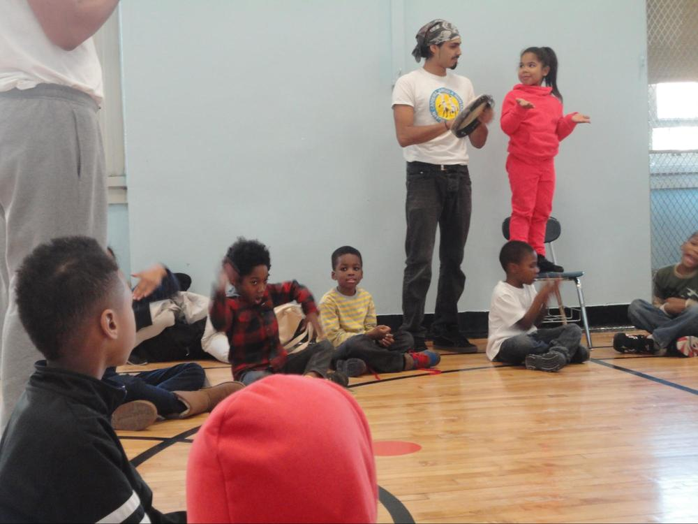 A young girl in PS 11 Afro Brazil Arts (ABA) capoeira after school program learns to lead capoeira songs for the class to respond with the chorus.