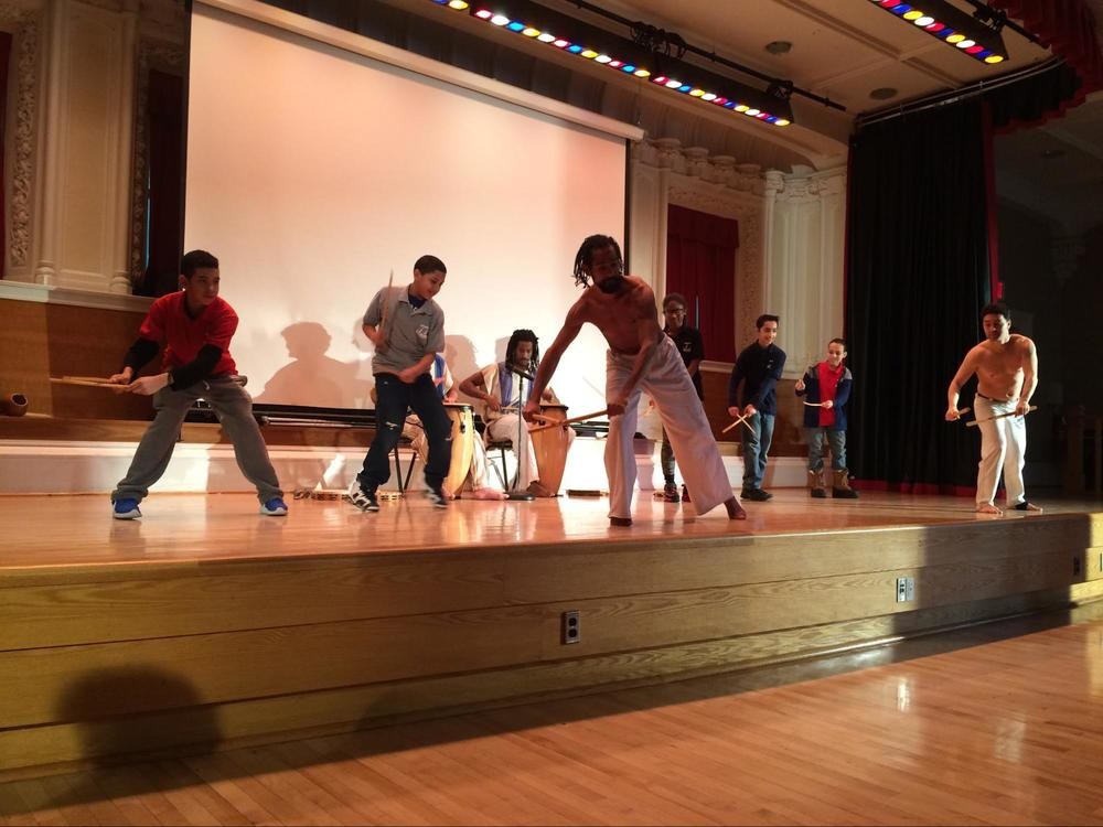 Students in the theater are called on stage to demonstrate FDR - Focus, Discipline and Respect while performing Maculelê in front of their peers.