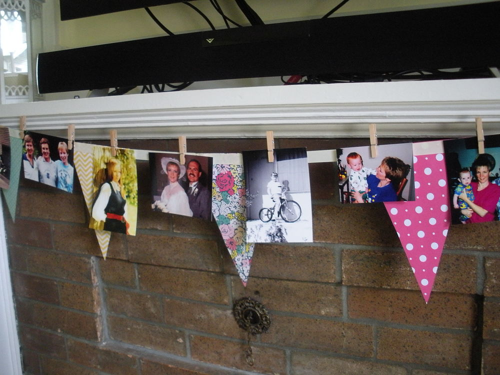 I used tiny clothespins to pin pictures of my Mom and family to the banner over the fireplace