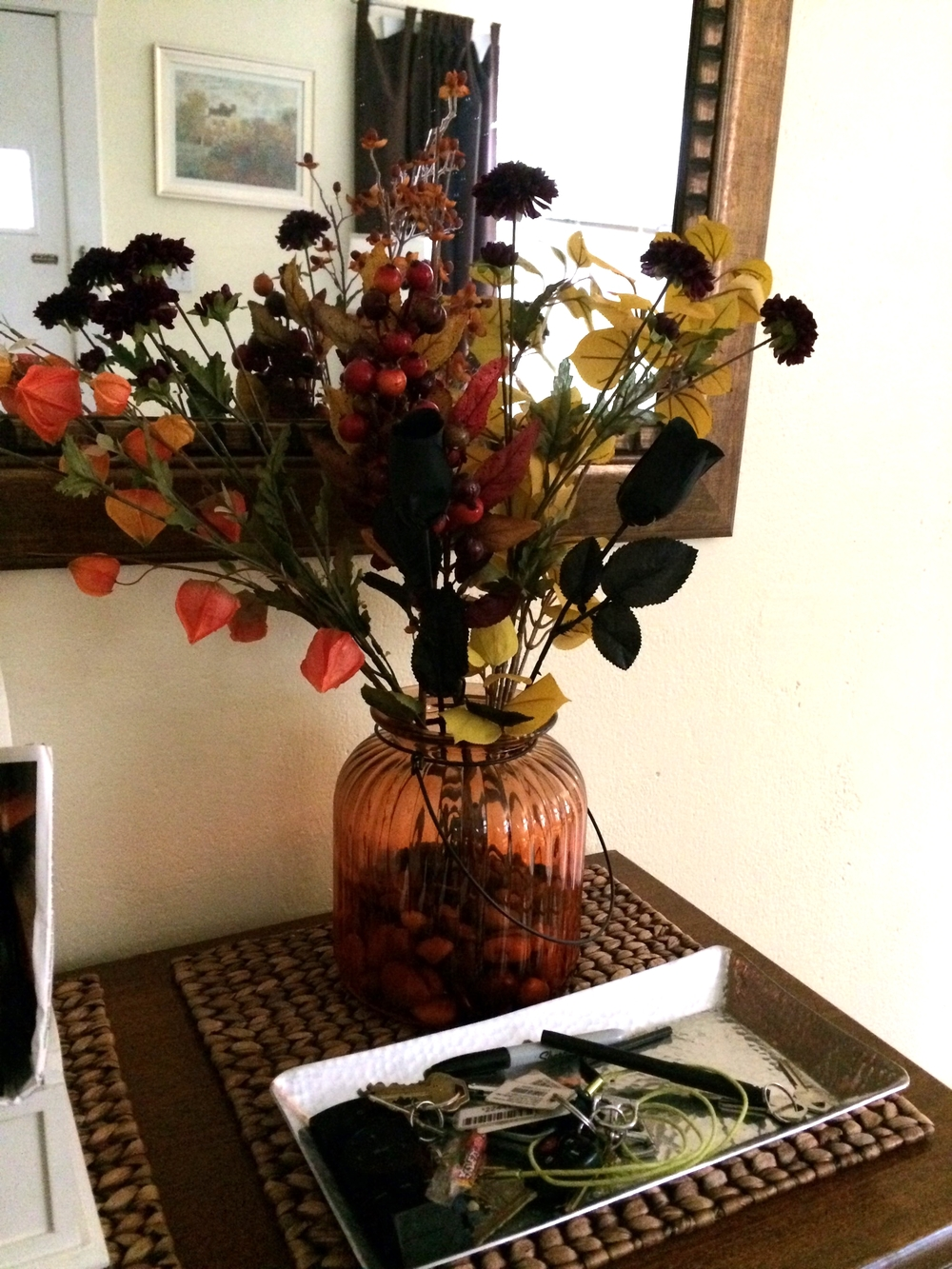 Black roses join other faux fall floral on the entry console for a no-mess arrangement