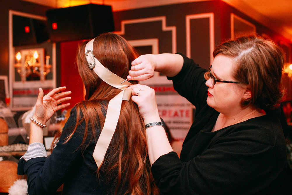 Katie of Mod Fleur fits one of her handmade headpieces to a local bride-to-be. Image courtesy of  Vness Photography .