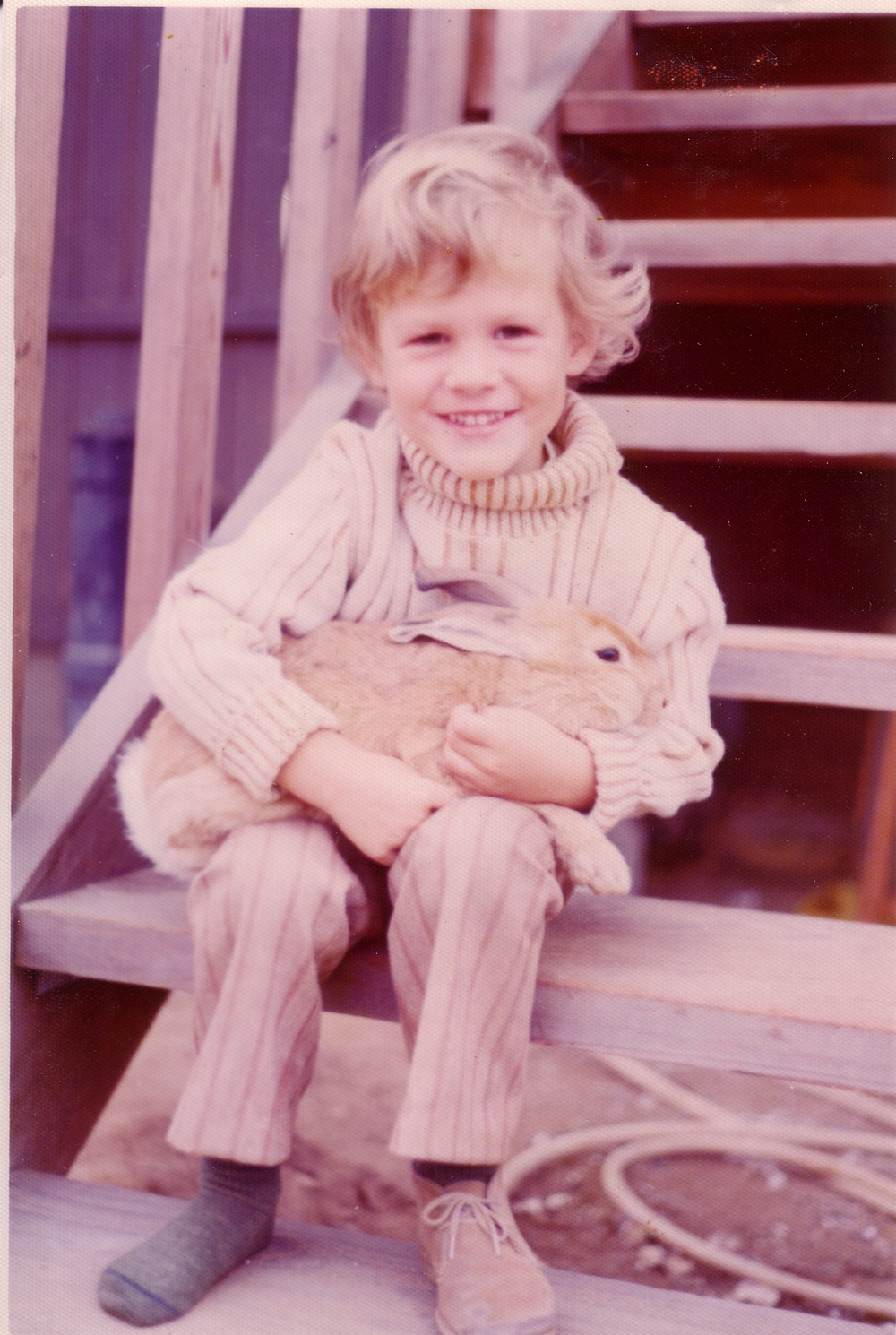 Roll-neck sweater. Stripped pants. Rabbit prop. Two shoes?