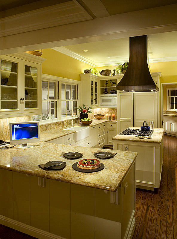 Kitchen: Fluorescent puck lights by Tresco provide both task lighting for counter tops and ambient light above cabinets. Warm color blends seamlessly with the incandescents used in other parts of house.