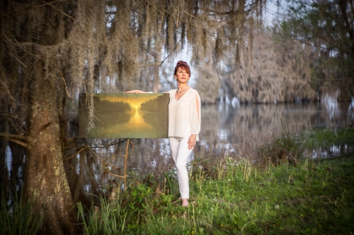 Artist Melissa Bonin with one of her paintings at Lake Martin, Louisiana in 2015. Through many days of research and conversations we knew we had to be at the lake one hour before sunrise to be setup and ready for the magic of the morning 'golden hour'.