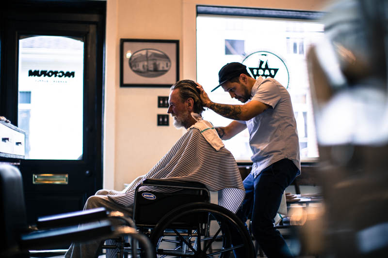 Zack-Smith-Photography-New-Orleans-jason-Barber-Shop-Bywater-Documentary-Wheelchair-disabled-client-tattoos-Happy-worker