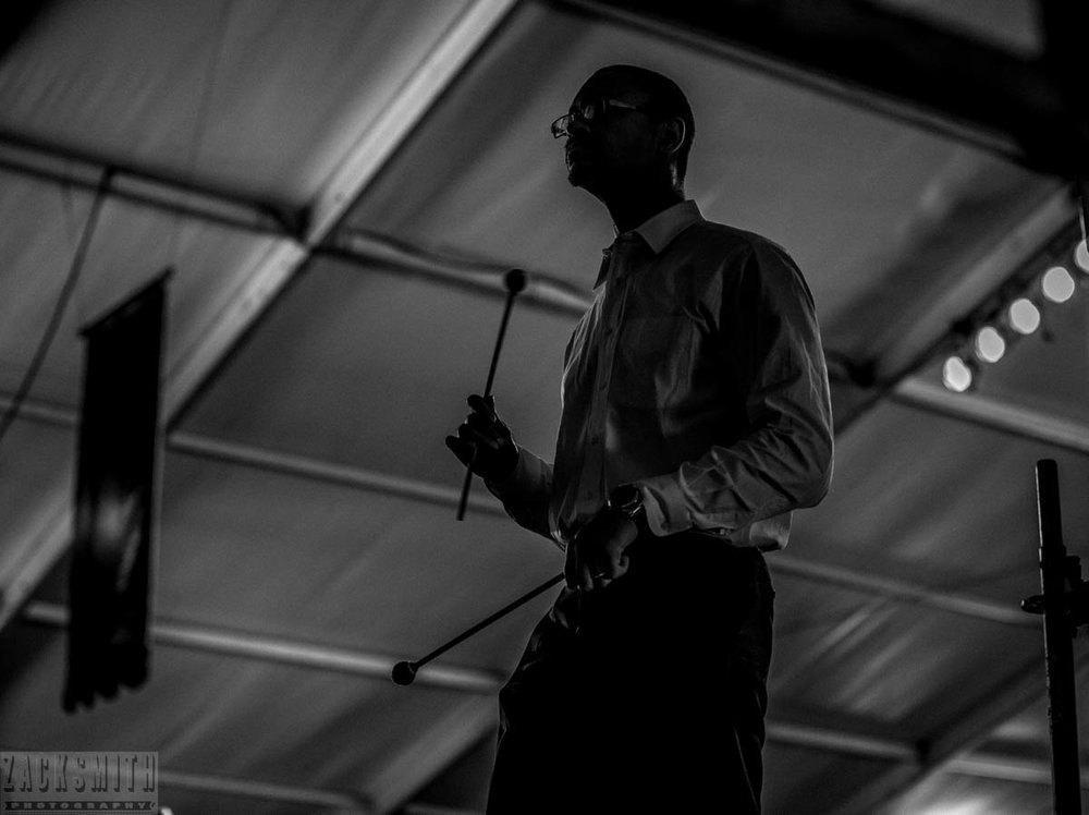 Musician Jason Marsalis sits out on stage right during a solo by his keyboard player at the Jazz Tent.