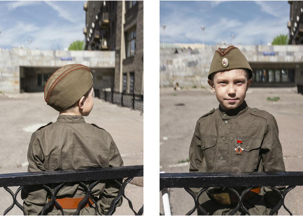 Jeune garçon, arborant la calotte traditionnelle soviétique, attend le défilé des forces d'armées russes.