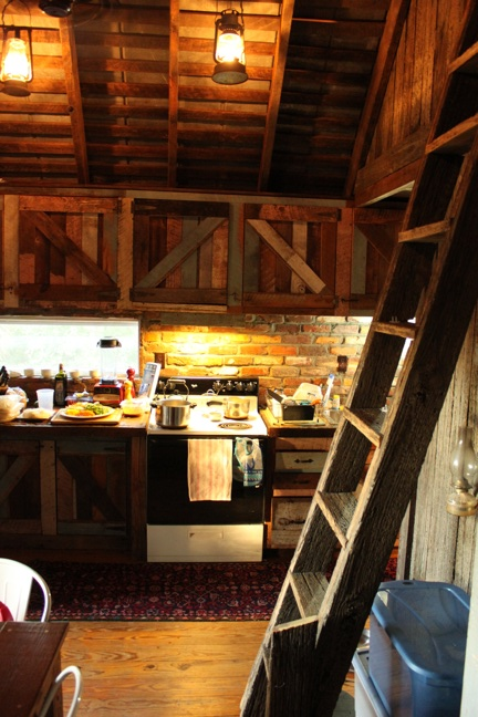 The kitchen, with ladder to the writing loft and site-built cabinetry.