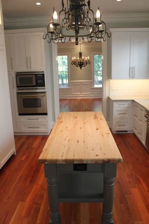 A parson's table anchors the kitchen and centers on a widened opening into the dining room, project to get increased usage post-renovation.