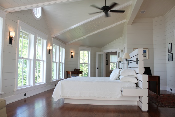 Headboard, positioned beneath a dropped beam, completes the transition between the entry and principal bedroom spaces.