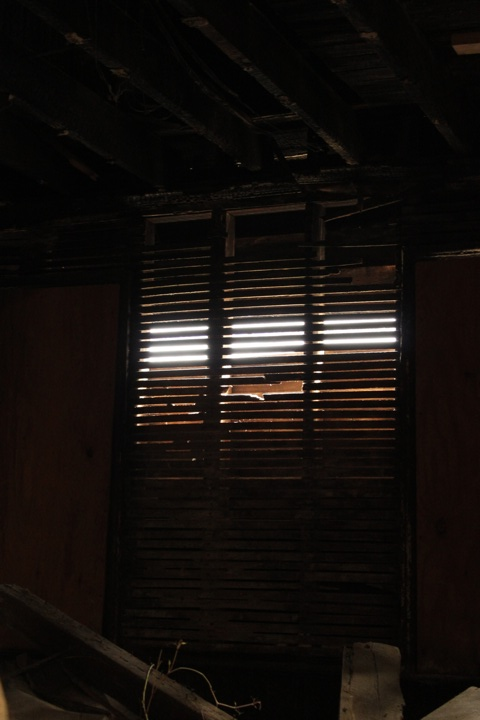 With siding missing and plaster gone, backlit wood lathe remains.