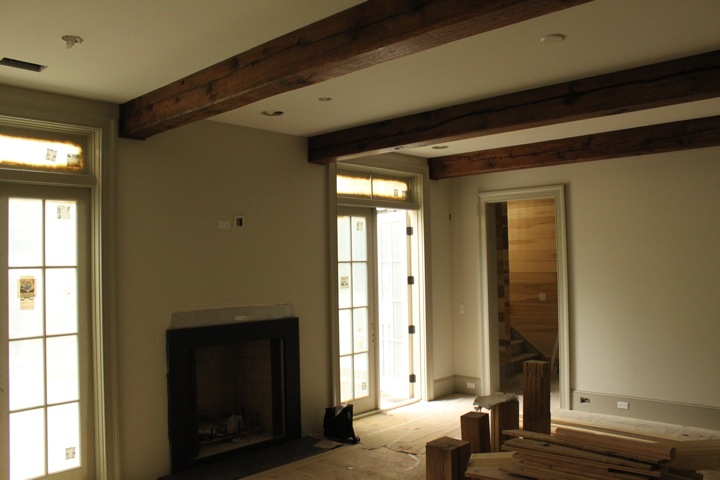 Living Room; mantle yet to go, oak beams by Fountain Timberworks