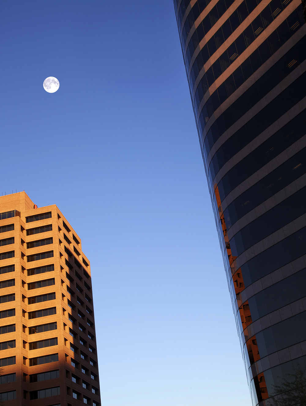 "While scouting some ""local color"" shots for a major hotel chain, Greg grabbed this shot in downtown Phoenix just as the setting sun squeezed between two office buildings. The added bonus was a full moon and an absolutely perfect blue sky."