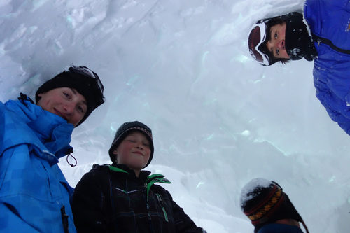 Kyle Totman, Alex Keltner, and Cade Harris stand tall in their newly dug quinzee while instructor Scott Laidlaw inspects