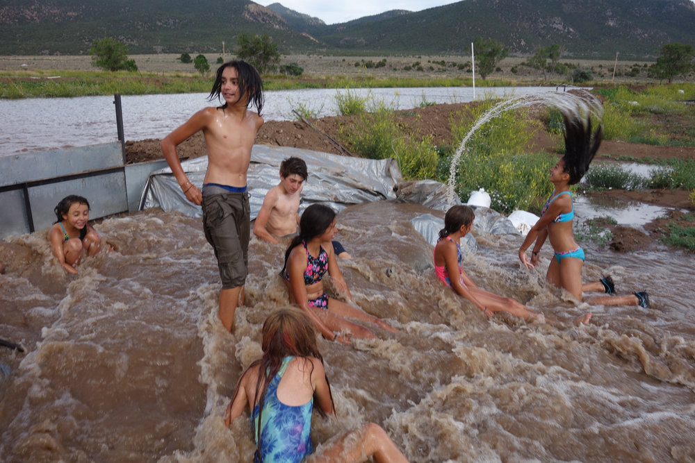 "Summer Campers serve as ""human sandbags"" in an experimental flood-flow irrigation release."