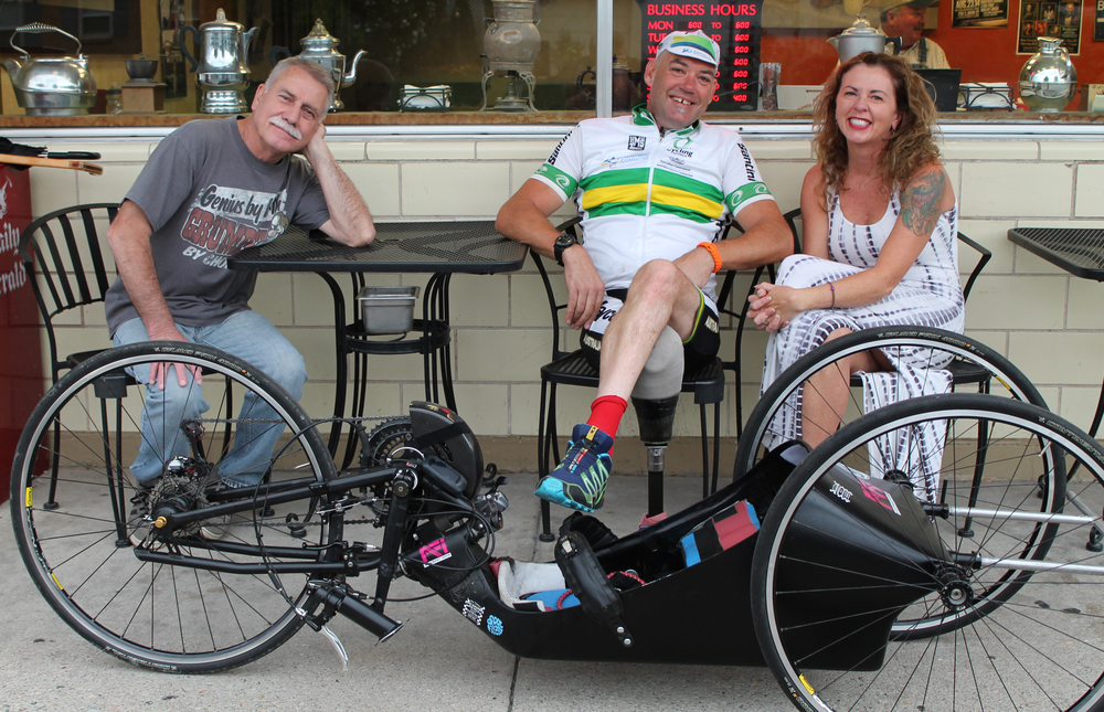 Pictured: L-R Customer Alan Curtis, Handcyclist Stuart Tripp, and Owner Colette Wing at Joe Coffee and Espresso in Payson, Utah.  Tripp has just finished competing in the UCI Para-Cycling Road World Championship in Greenville, South Carolina, over the Labor Day weekend.  In late July of this year, he competed in a World Cup event in Segovia, Spain, where he finished second in a time trial and fourth in the road race.  Complete story published in the September 10, 2014, edition of The Payson Chronicle.