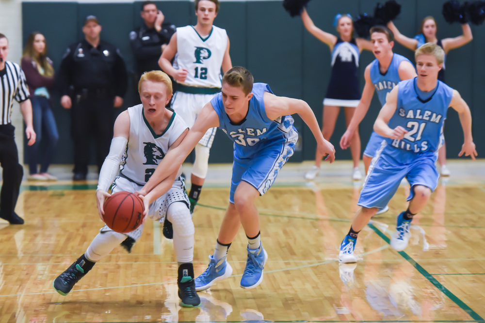 After the big game last Tuesday night between the Lions and the Skyhawks, both teams lost Friday night, Payson in overtime 61-62 against Wasatch, and Salem Hills against Uintah, 70-73.  Pictured: PHS 21 Damon Bahr and SHHS 30 James Nelson scrap for the ball.  Photo by Todd Phillips (more at SalemHillsPhotos.com)  See also the February 3, 2016, print edition of The Payson Chronicle for more.
