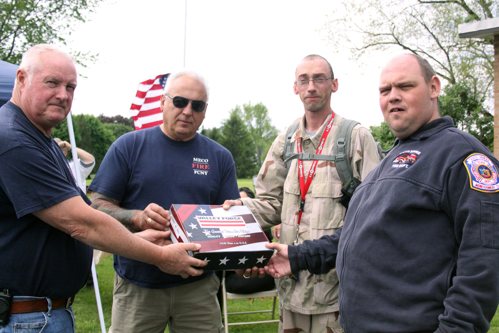 Meco Firemen Gary Stoller and Richard Ruby present Lexington participants Patrick Foote and Joe Looman with a new American flag that was raised at Gloversville's Bishop Burke facility.