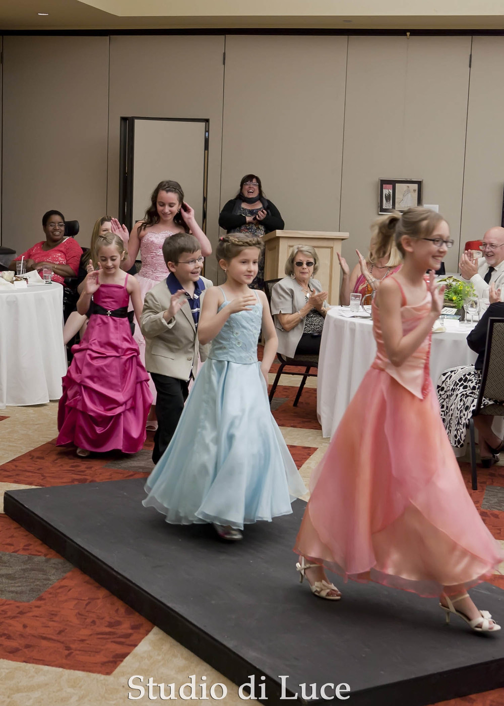 The child models take one last turn down the runway.