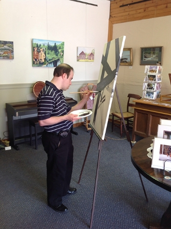 Ross Carangelo works on a painting at the Northville Art Center.