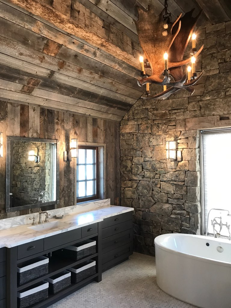 Master Bathroom with rustic timbers, granite stone walls and antler chandelier.