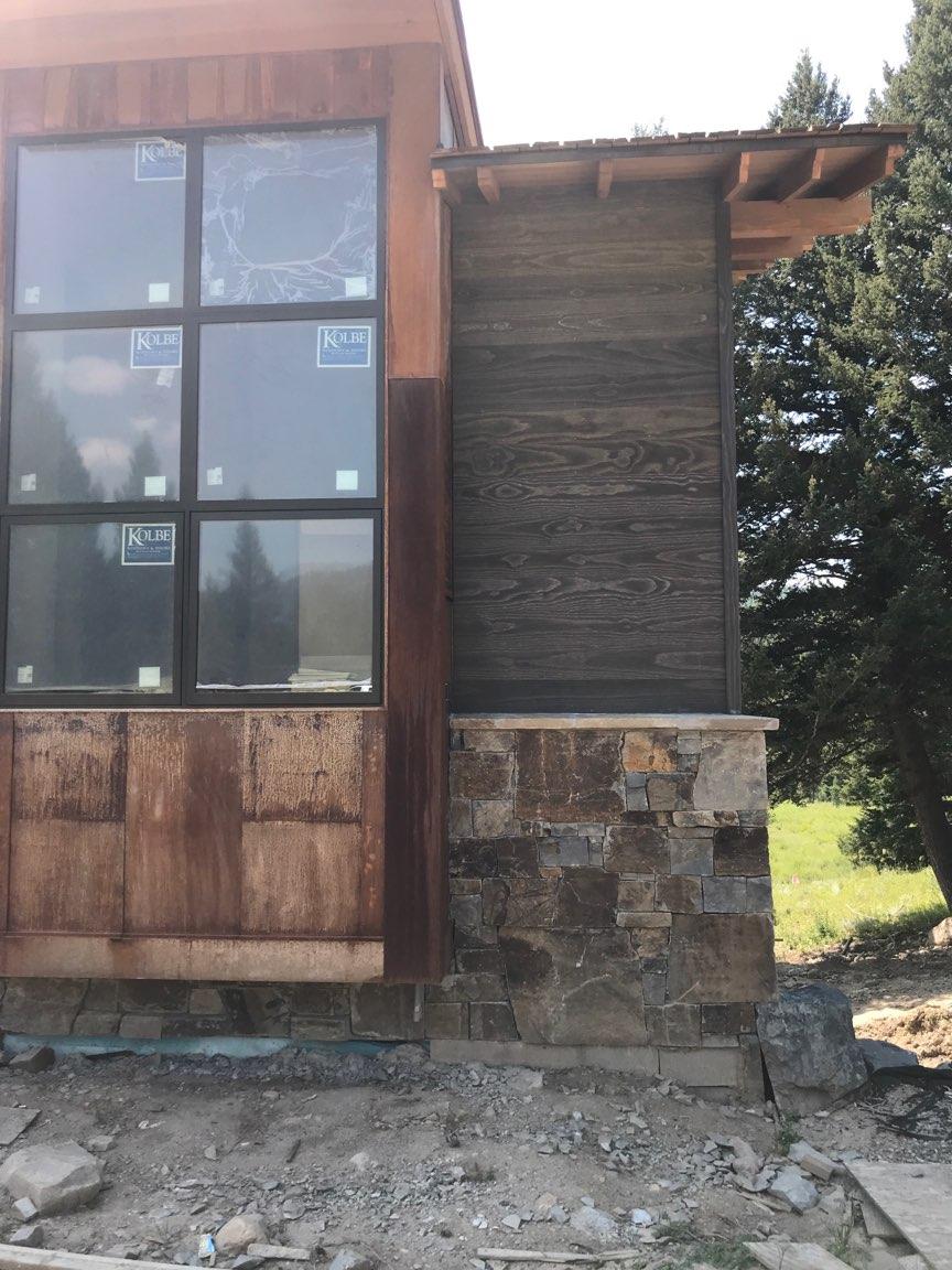 Big Sky custom home design view of windows siding and stone exterior.jpg