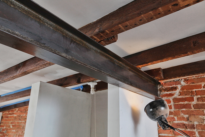 The new steel S-beam supports the original exposed roof rafters and adds to the industrial feel of the studio space