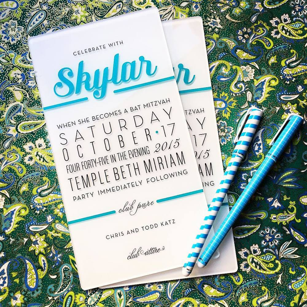 SKYLAR BAT MITZVAH Hi-gloss white acrylic invitations screen printed in teal and black  Photograph by Suzie McKig