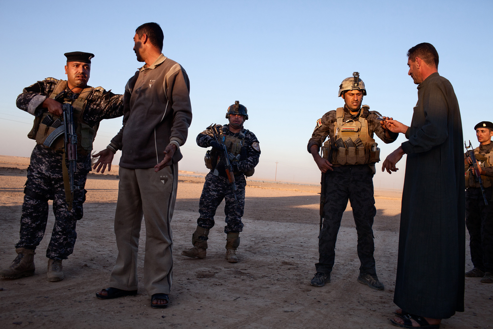 Members of the Iraqi National Police search men at a house on the outskirts of Tikrit in Salah ad Din, Iraq.