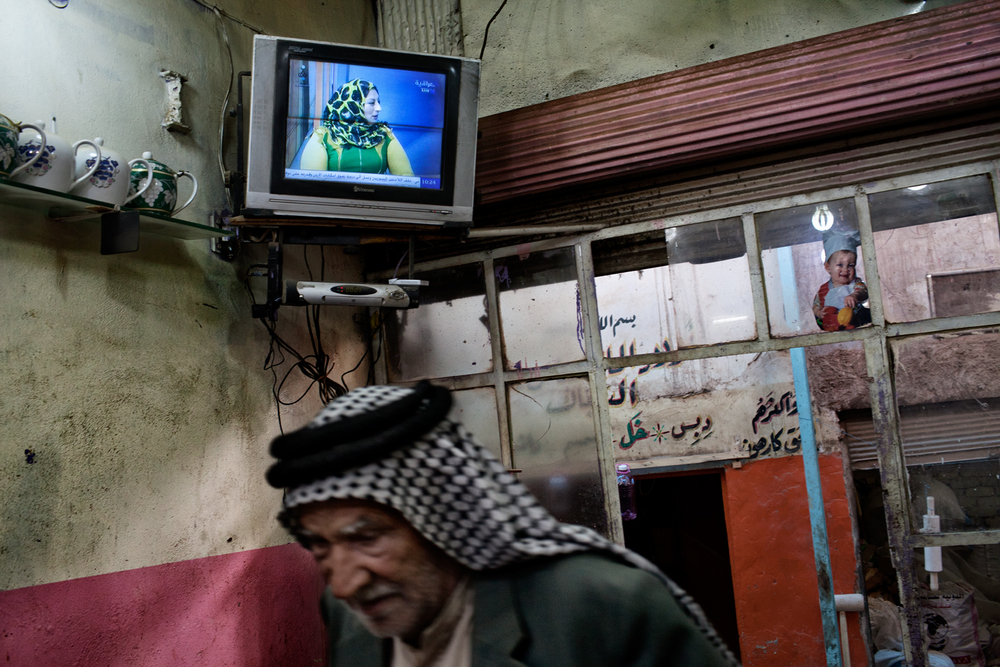 A women's rights activist speaks on talk show on Iraqiya channel on a television seen inside a tea shop at the central market in Hilla, Babil Province, Iraq.